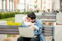 Young dad and son at outdoor. Father try to work with computer royalty free stock image