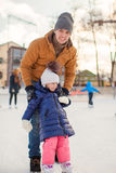 Young Dad teaches his little daughter to skate on Stock Image