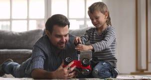 Daddy teaching cute kid son playing toy car on floor