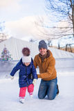 Young Dad teaching his little daughter to skate on Royalty Free Stock Photos