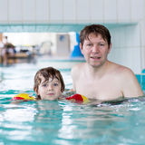 Young dad teaching his little son to swim indoors Stock Photo