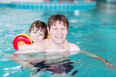 Young dad teaching his little son to swim indoors Royalty Free Stock Image