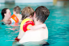 Young dad teaching his little son to swim indoors Royalty Free Stock Photos