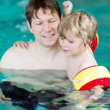 Young dad teaching his little son to swim indoors Royalty Free Stock Photography