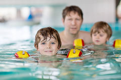 Young dad teaching his two little sons to swim indoors Royalty Free Stock Photography