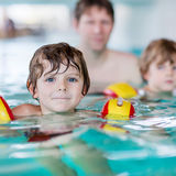 Young dad teaching his two little sons to swim indoors Stock Images