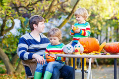 Young dad and two little kids making jack-o-lantern Royalty Free Stock Images