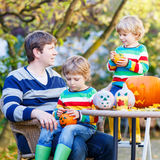 Young dad and two little kids making jack-o-lantern. Young dad and two little kid boys making jack-o-lantern for halloween in autumn garden, outdoors. Family Royalty Free Stock Photography