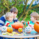 Young dad and two little sons making jack-o-lantern for hallowee Royalty Free Stock Images