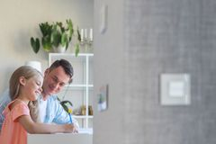 Young Dad With A Little Daughter Doing Homework Indoors Royalty Free Stock Photo