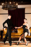 Young dance couple preforming latin show dance in ancient ballro Stock Images