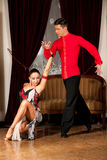 Young dance couple preforming latin show dance in ancient ballro Royalty Free Stock Photography