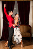 Young dance couple preforming latin show dance in ancient ballro Royalty Free Stock Image