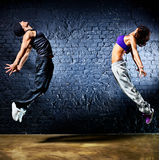 Young dancer couple jumping. On wall background royalty free stock photo