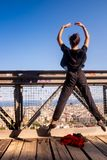 Young dancer jumping in mid-air on the bridge, urban landscape in the background royalty free stock photography
