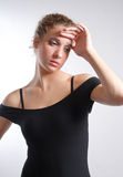 Young dancer looking tired. And touching her forehead royalty free stock image