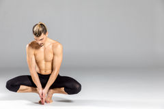 Young dancer posing. Young flexible male dancer posing and looking down on grey royalty free stock images