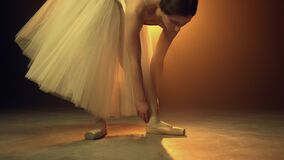 Young dancer putting on ballet shoes indoors. Ballerina tying pointe on stage.