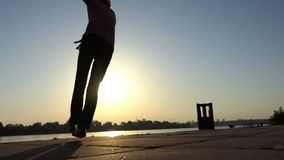 Young dancer shows modern pas on a river bank at sunset in slo-mo. An electifying view of a young man who dances disco actively on a river bank at a splendid stock video