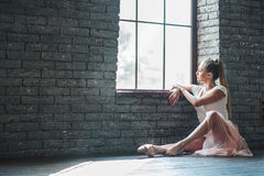 Young dancer sitting in dance studio Royalty Free Stock Images