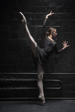 Young dancer training in the dark room. Full of gracefulness. Concentrated charismatic young dancer standing near the wall and training while expressing grace Royalty Free Stock Photo