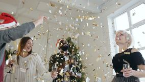 The young dancing guys and girls have fun playing with golden confetti, drinking wine before christmas tree at the stock video footage