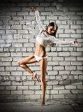 Young dancing woman on brick wall background (dark version) Royalty Free Stock Photo