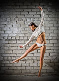 Young dancing woman on brick wall (normal version) Royalty Free Stock Photography
