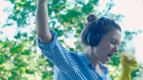 Young dancing woman in headphones runs squeegee on window. Young dancing woman in headphones runs black squeegee on window with white spray in summer close view stock footage