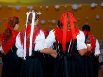 Young dancing women in traditional folk dress on wedding feast ceremony. Stock Photos