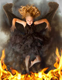 Young dark angel rising from the flames Stock Photos