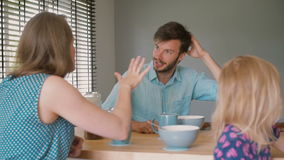 A young dark-haired father is having a conversation with his beautiful wife at the kitchen table. Slow motion stock footage