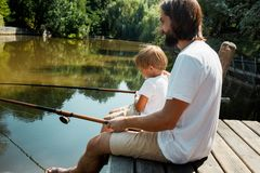 Young dark-haired father his little and son dressed in the white t-shirts are sitting with fishing rods on the wooden royalty free stock images