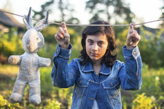 Young dark-haired girl in a denim jacket with an old toy Royalty Free Stock Photos
