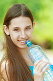 Young dark-haired girl drinking water. Portrait of young beautiful dark-haired girl wearing blue t-shirt drinking water at summer green park stock photography