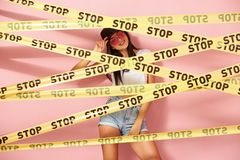 Young dark-haired girl in pink sunglasses and cap dressed in jeans shorts and white top stands behind the yellow scotch royalty free stock image