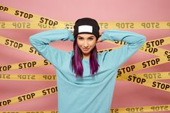 Young dark-haired girl with purple hair tips dressed in blue sweatshirt and black hat stands on the background of pink royalty free stock photo