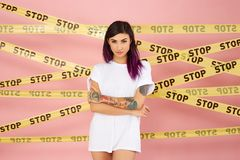 Young dark-haired girl with purple hair tips and tattoo on her arm dressed in the white t-shirt stands on the background stock photography
