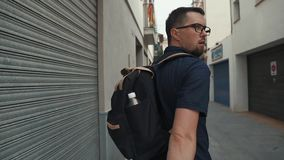 Alone man is walking on narrow city street, looking around, back view. Young dark haired male tourist is strolling on city lane in daytime. He is examining stock video footage