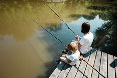 A young dark-haired man and a blond boy dressed in the white t-shirts are sitting with fishing rods on the wooden pier royalty free stock photos