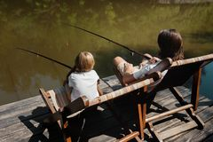 A young dark-haired man and a blond boy are sitting in recliners on the wooden pier with fishing rods and fishing. stock photo