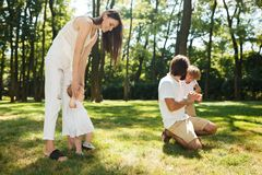 Young dark-haired mother and father dressed in white clothes are spending summer day with kids on a lawn in the park. stock photos