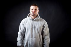 Young man sick. A young, dark-haired, sad man in a sporting gray sweatshirt fell ill with a cold, his head hurts and he holds onto it on a black isolated Royalty Free Stock Photo