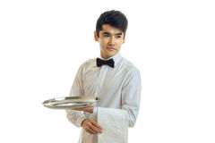 Young dark haired waiter holding a tray with a towel and looking toward. The  on white background Stock Photos
