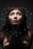Young dark-haired woman. Romantic portrait of a young dark-haired woman on black background stock image
