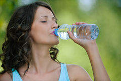 Young dark-haired woman drinking water Stock Images