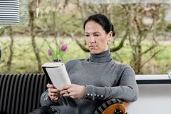 Dark haired woman at home relaxing and reading book royalty free stock photography