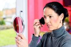Dark haired woman looking in mirror and applying make up Stock Photography