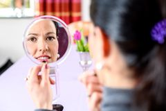 Dark haired woman looking in mirror and applying make up royalty free stock image