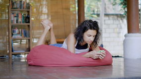 Young dark-haired woman lying on a bright pink beanbag on a balcony of tropical house using her smartphone. Beautiful. Young dark-haired woman is lying on a stock footage